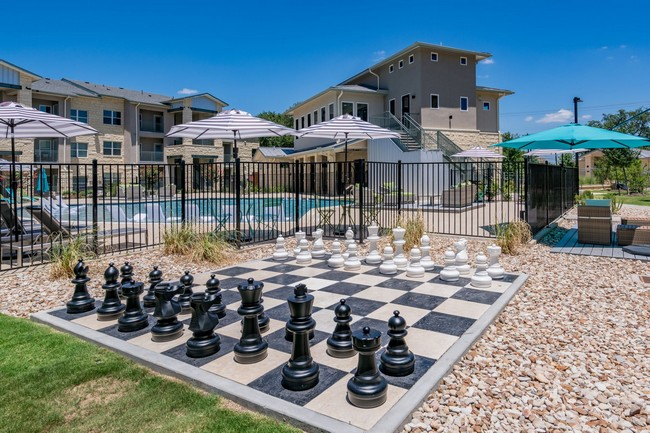 Oversized outdoor chess game next to swimming pool