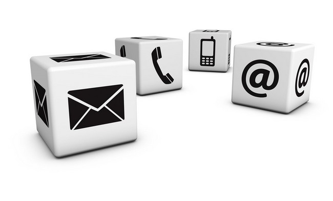 White cubes with black email, phone, cell phone and @ icons on it.