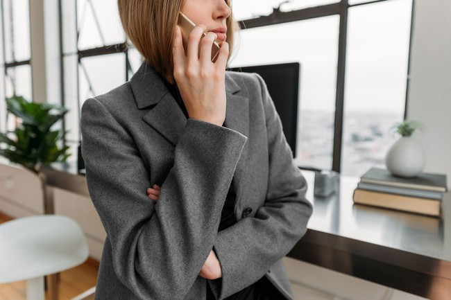 A person holding a mobile phone near the ear