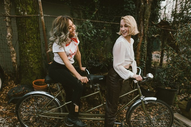 Two young ladies smiling on a tandem bicycle