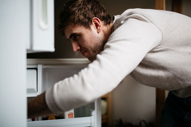 Young man looking inside refrigerator