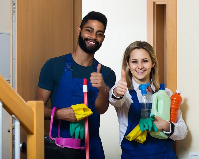 Man and woman smiling with cleaning supplies