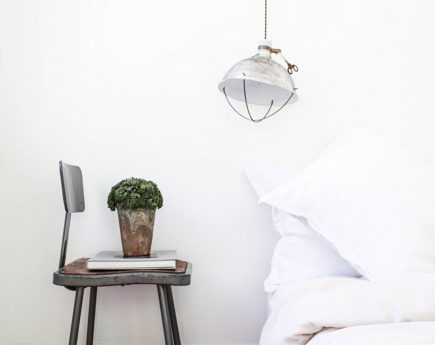 Chair with book and plant next to bed with light fixture above
