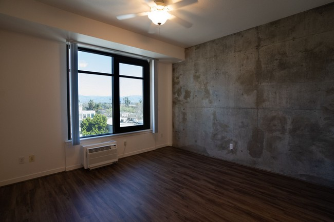 Apartment bedroom with vinyl flooring and concrete wall