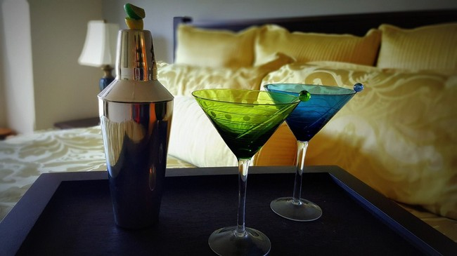 Shaker and glasses on tray on bed