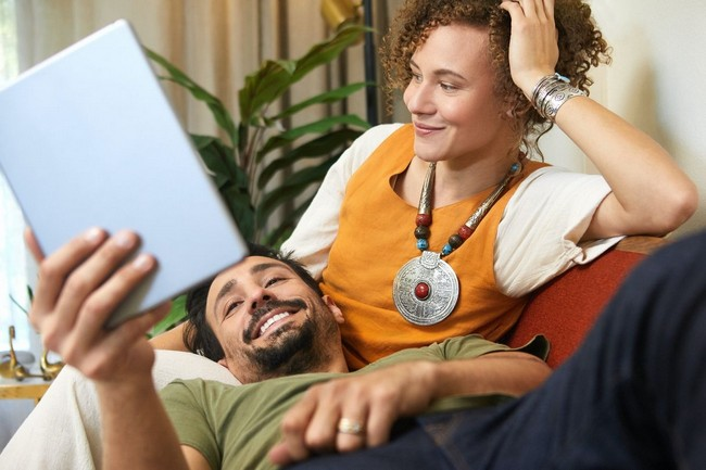 woman and man on couch, looking at tablet
